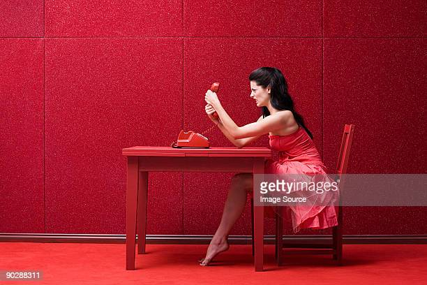 Woman in red room with telephone