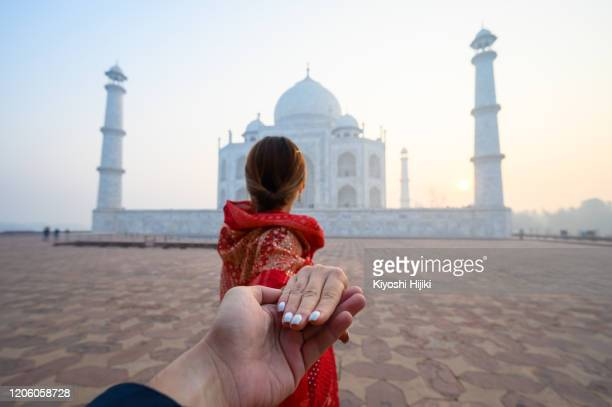 woman in red saree indian traditional dress holding man hand in taj mahal in agra, india - punjab - india stock pictures, royalty-free photos & images