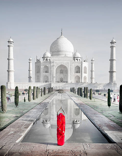 Woman in red sari praying at Taj Mahal
