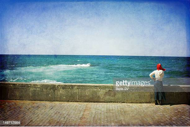 Woman in red scarf by seaside