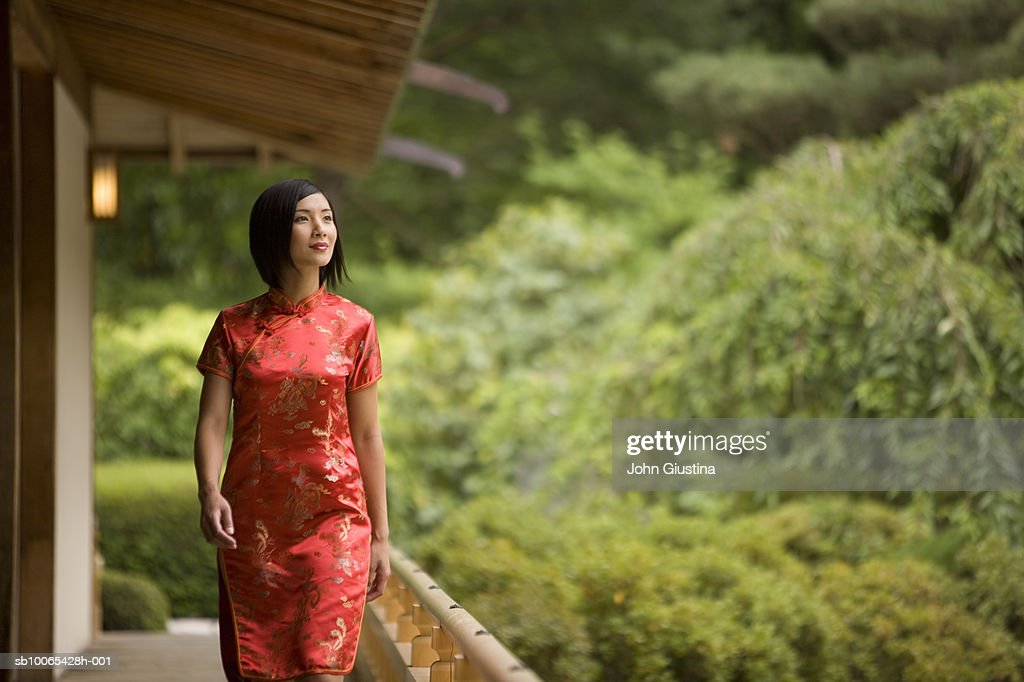 Woman in red silk dress walking on porch of Japanese house : Foto stock