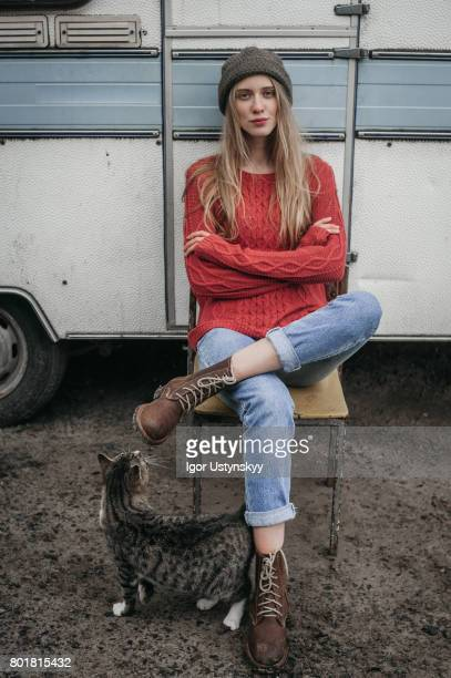 Woman in red sweater sitting near the trailer  with cat