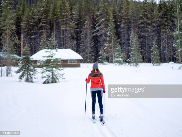 woman in red sweater skis cross country towards a cabin in the mountains - lori andrews stock pictures, royalty-free photos & images
