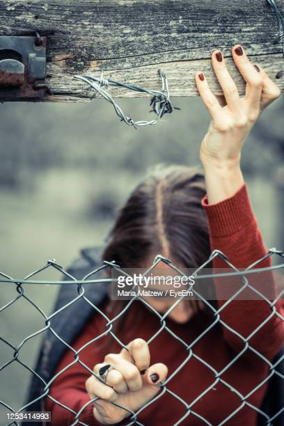 woman in red sweater with dark manicured nails and heart-shaped ring pushing against metal fence. - unfairness stock pictures, royalty-free photos & images