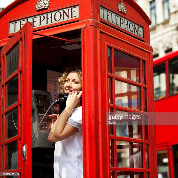 Woman in Red Telephone Booth. London, UK