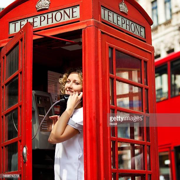 Femme en rouge cabine téléphonique. Londres, Royaume-Uni