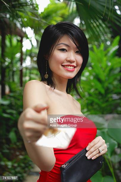woman in red tube top, holding credit card towards camera - red tube top stock photos and pictures
