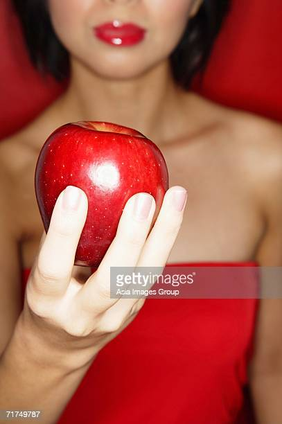 woman in red tube tope holding red apple - red tube top stock photos and pictures
