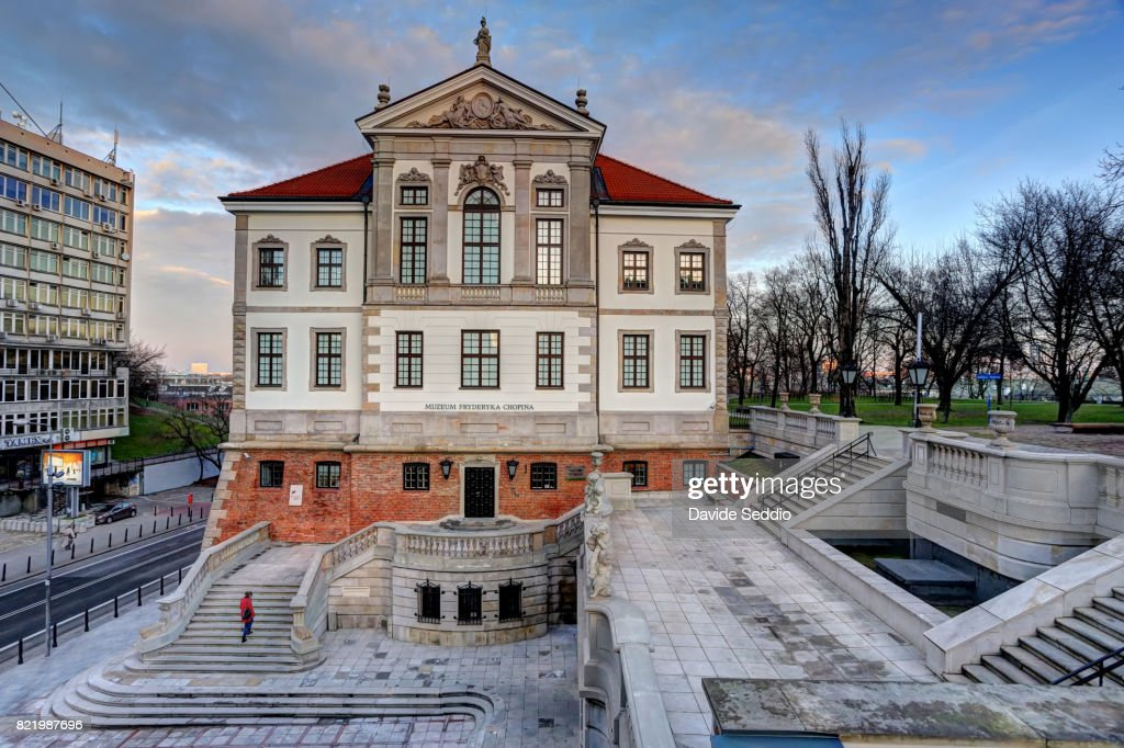 Woman in red walking up the entrance stairs in front of the Frederic Chopin Museum in Warsaw : Stock Photo