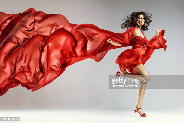 woman in red waving dress with flying fabric - silk stock pictures, royalty-free photos & images