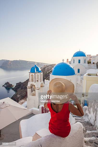 Woman in red with hat looking at sunset, Santorini