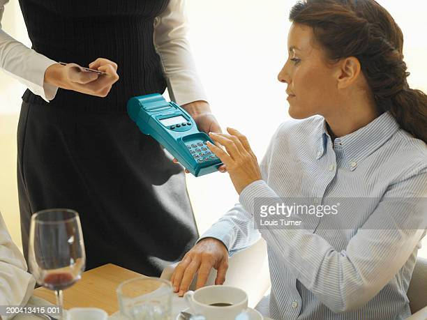 Woman in restaurant using chip and pin machine held by waitress