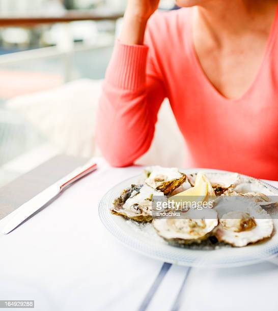 Woman in restaurant with plate of oysters