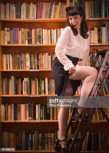 woman in retro clothing on library ladder - nylon stock photos and pictures