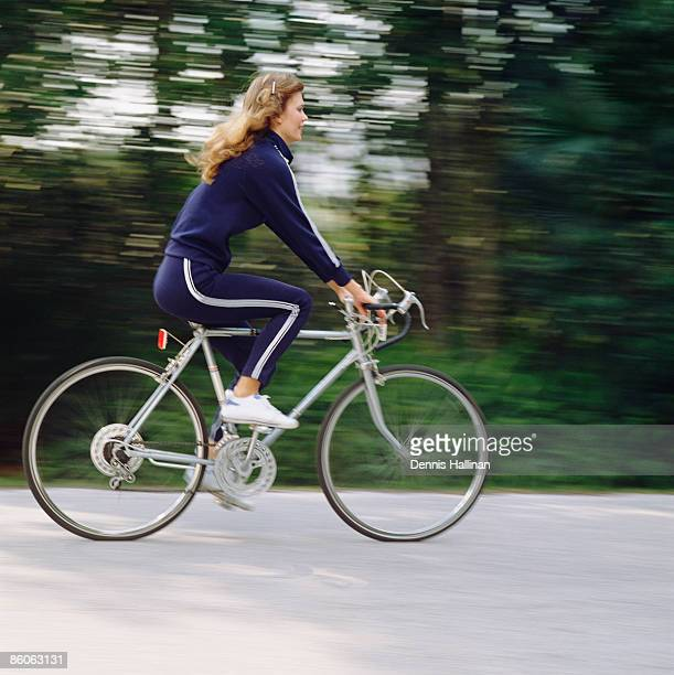 Woman in retro tracksuit riding bicycle