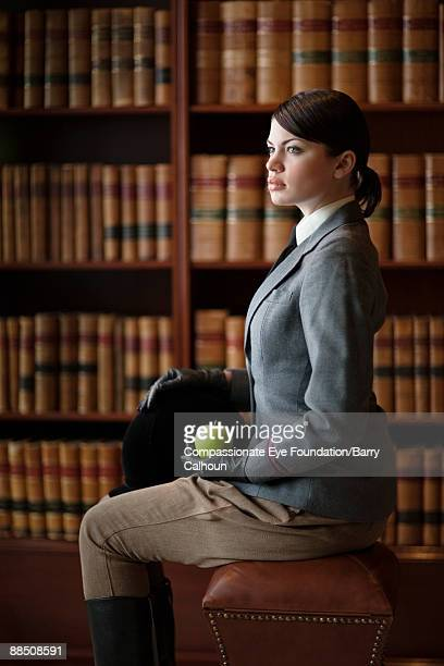 """woman in riding outfit in library holding apple - """"compassionate eye"""" stock pictures, royalty-free photos & images"""