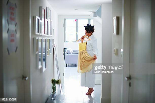 Woman in robe choosing dress in front of mirror