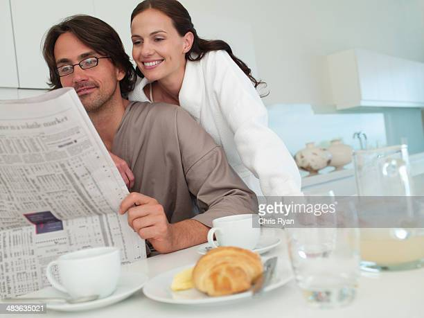 Woman in robe embracing man in robe with newspaper