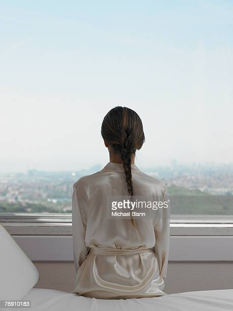 Woman in robe looking out of window, rear view