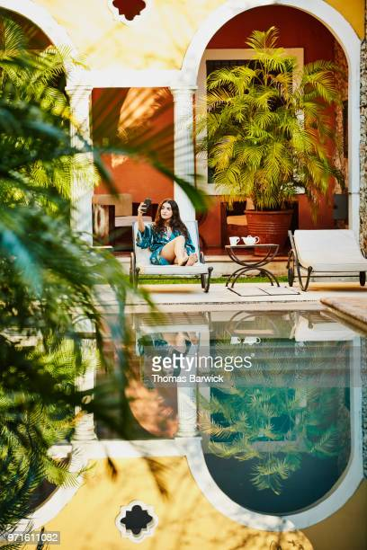 Woman in robe sitting in lounge chair by pool in hotel courtyard taking selfie with smartphone