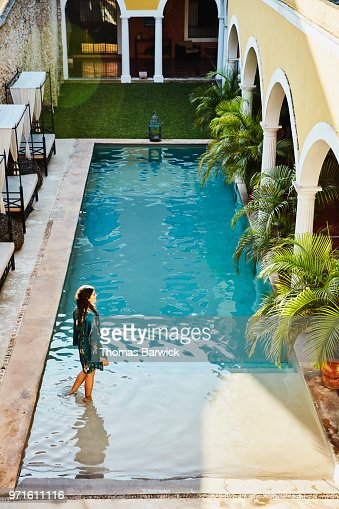 Woman in robe standing in pool in courtyard of boutique hotel