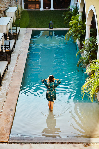 Woman in robe standing on top step of pool in courtyard of boutique hotel - gettyimageskorea