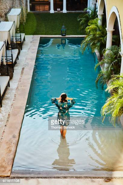 Woman in robe standing on top step of pool in courtyard of boutique hotel