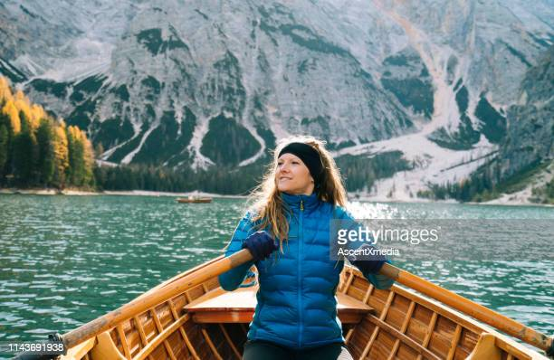 woman in row boat paddles toward mountain - only mid adult women stock pictures, royalty-free photos & images