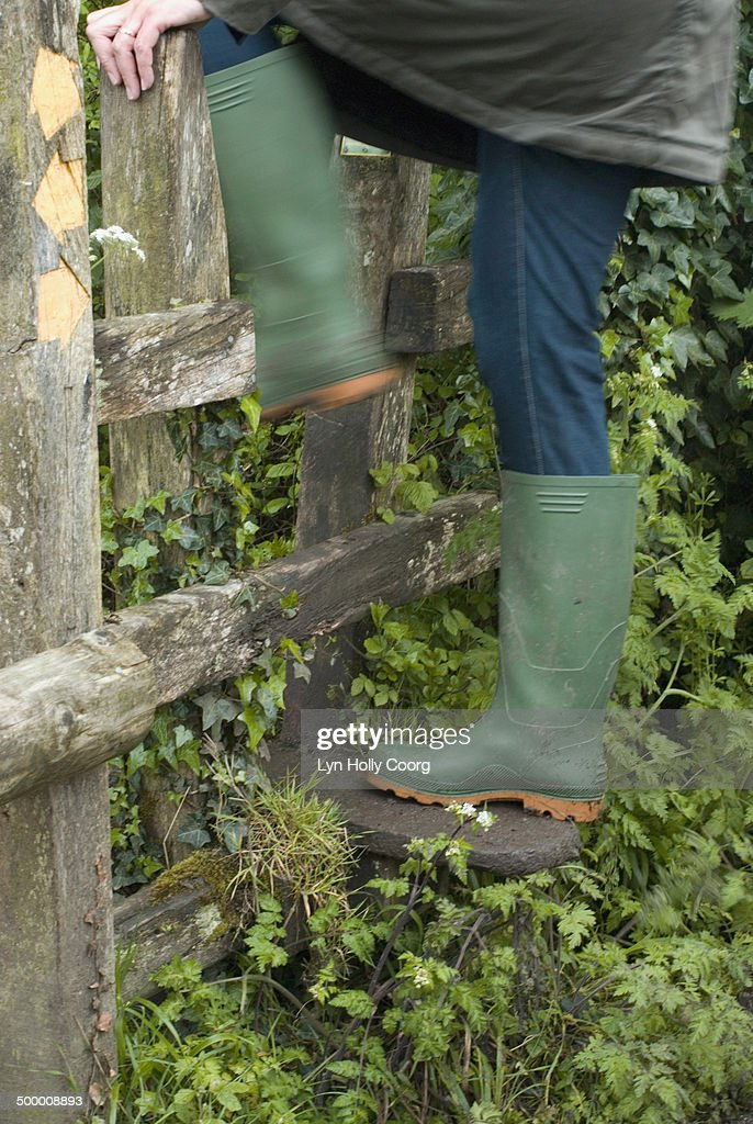 Woman in rubber boots climbing over wooden stile : Stock Photo