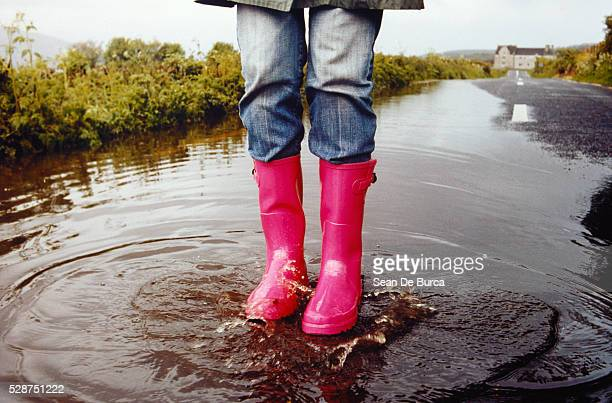 Woman in rubber boots standing on street in puddle