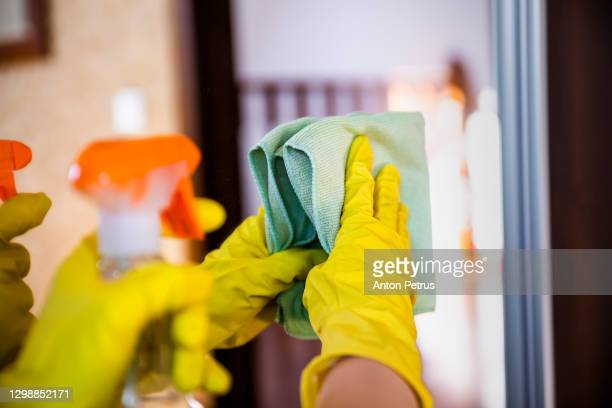 woman in rubber gloves wipes the mirror in the room - china: through the looking glass stock pictures, royalty-free photos & images