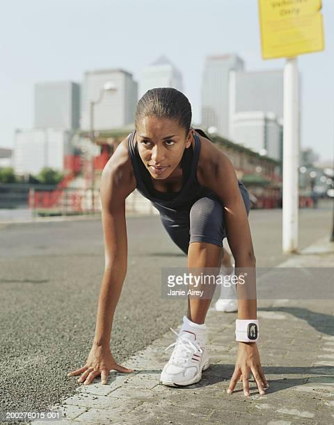 Femme en vêtements de course à pied en position de départ en bord de route