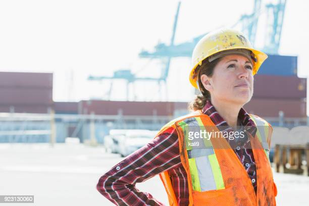 woman in safety vest, hardhat working at shipping port - dock worker stock photos and pictures