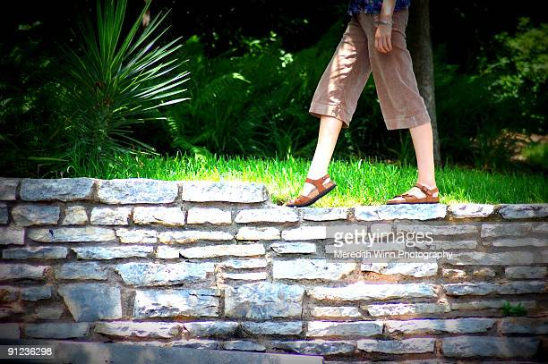 Woman in sandals and shorts walking on stone wall