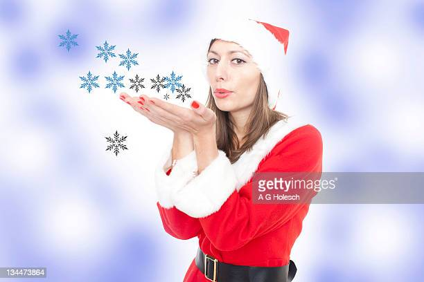 woman in santa claus costume blowing snowflakes - wishful skin stock pictures, royalty-free photos & images