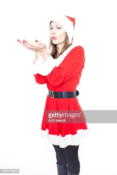 woman in santa claus costume blows on her hands - wishful skin stock pictures, royalty-free photos & images
