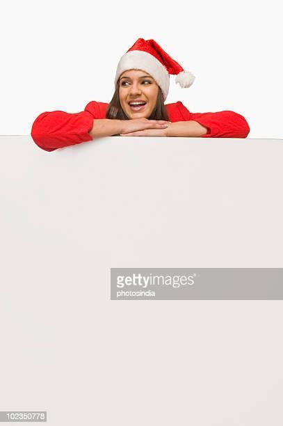 woman in santa costume leaning over a white board and smiling - mamma natale foto e immagini stock