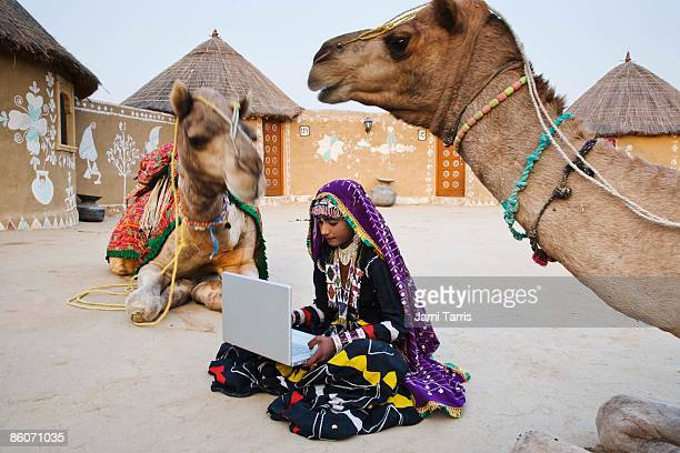 Woman in sari by camels with laptop computer