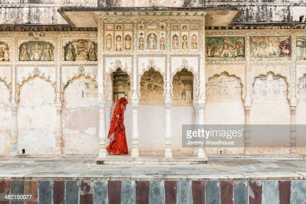 Woman in sari walking through cloister, Pushkar, Rajasthan, India