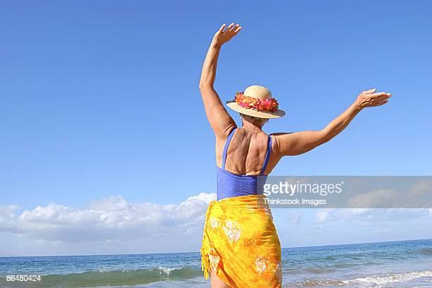 Woman in sarong and bathing suit by coast