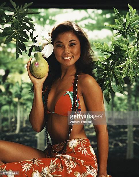 Woman in sarong holding papaya portrait smiling