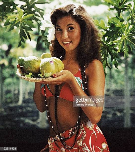 Woman in sarong holding plate of papayas portrait smiling
