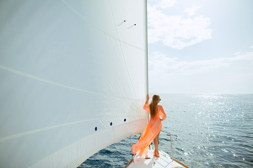 woman in sarong yachting white sails luxury travel 519340552