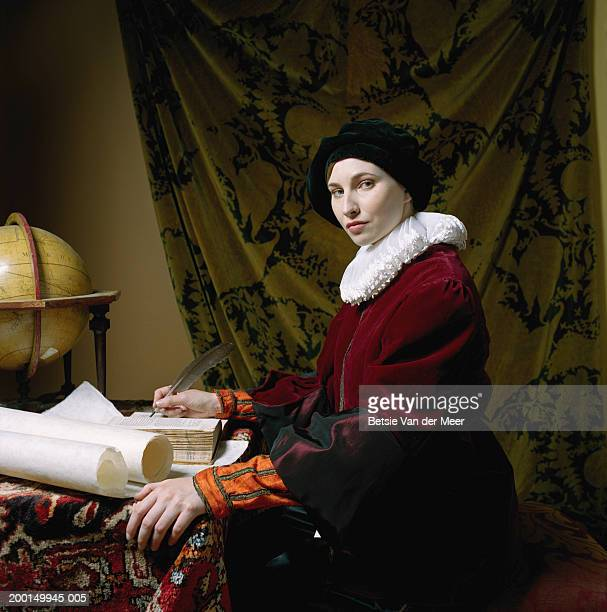woman in scholar outfit, holding feather quill pen at desk, portrait - elizabethan era stock photos and pictures