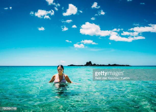Woman In Sea Against Blue Sky