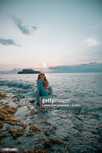 woman in sea against sky during sunset - lorena day stock pictures, royalty-free photos & images