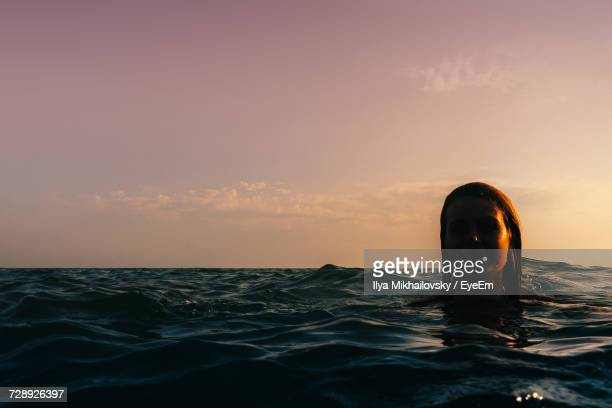 Woman In Sea Against Sky During Sunset