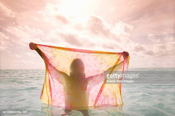 Woman in sea holding sarong at sunset