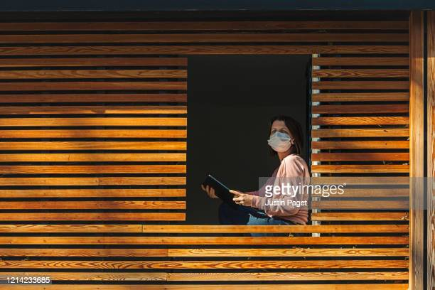 woman in self isolation sitting by open window - quarantäne stock-fotos und bilder