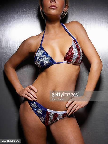 Woman in sequined star and stripes bikini, hands on hips, mid section